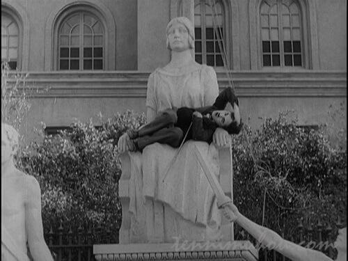 銅像の膝の上で安らかに眠るチャップリン